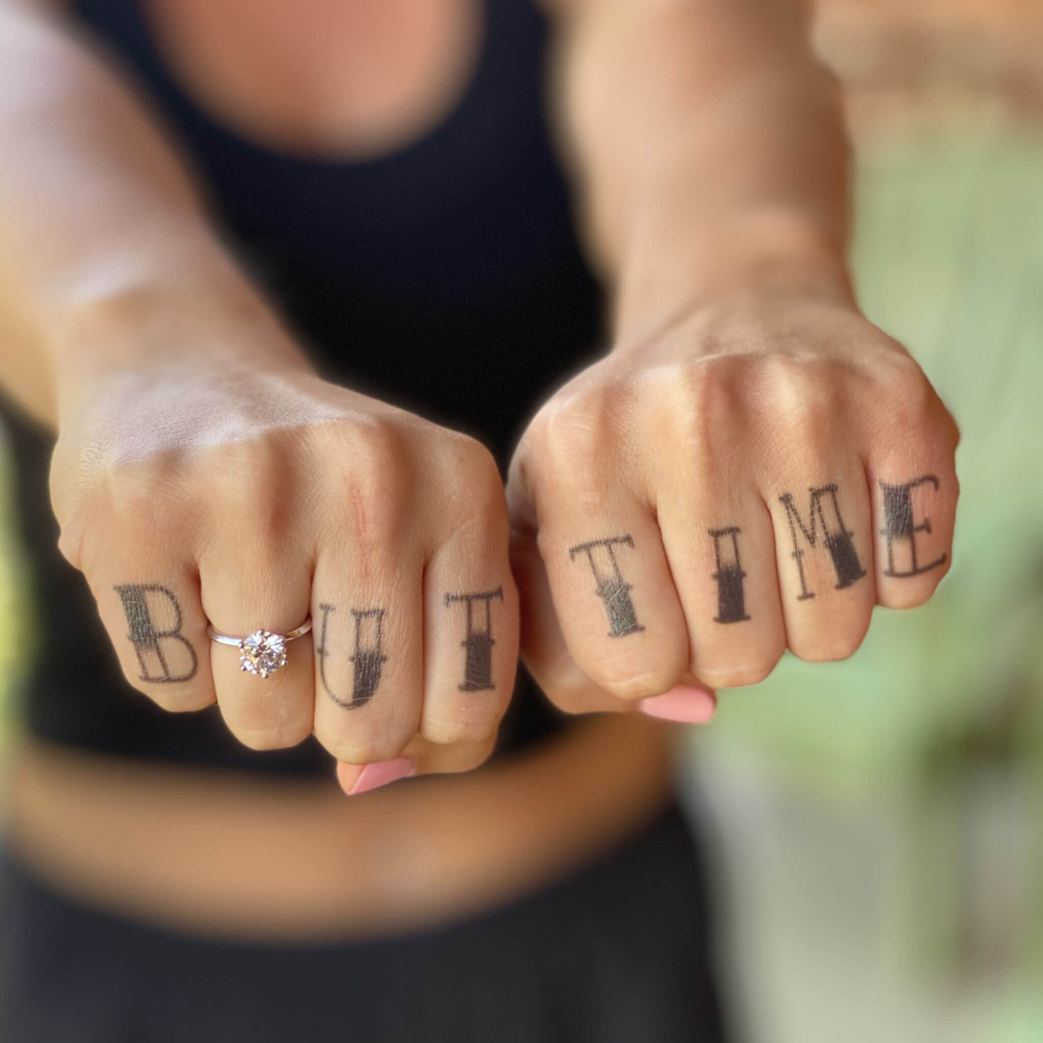 close up of fists held out in front of girl with letters B U T T I M E and the engagement ring in between the B and U to spell out bout time