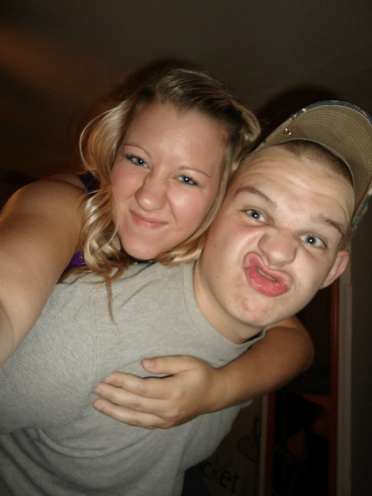 blonde haired girl on the back of boy making funny face with lips and wearing hat with grey shirt