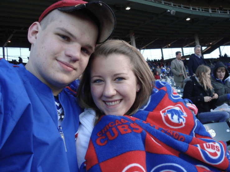couple sitting cuddled with each other in stadium man with blue jacket on and girl wrapped in chicago cubs blanket