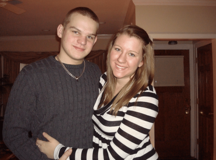 couple hugging each other posing for picture smiling the man on the left wearing cable knit brown sweater with gold chain and girl wearing brown and cream striped long sleeve shirt
