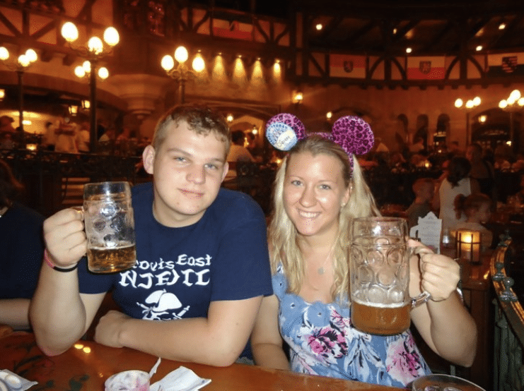 guy wearing dark blue shirt on the left sits next to girl wearing light blue floral shirt and pink minnie ears both holding mugs of drinks