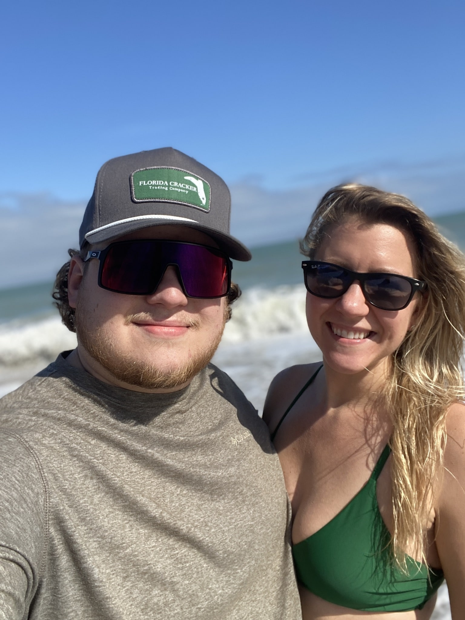 couple wears sunglasses standing next to each other for picture on the beach guy wearing grey shirt and girl wearing green bikini top