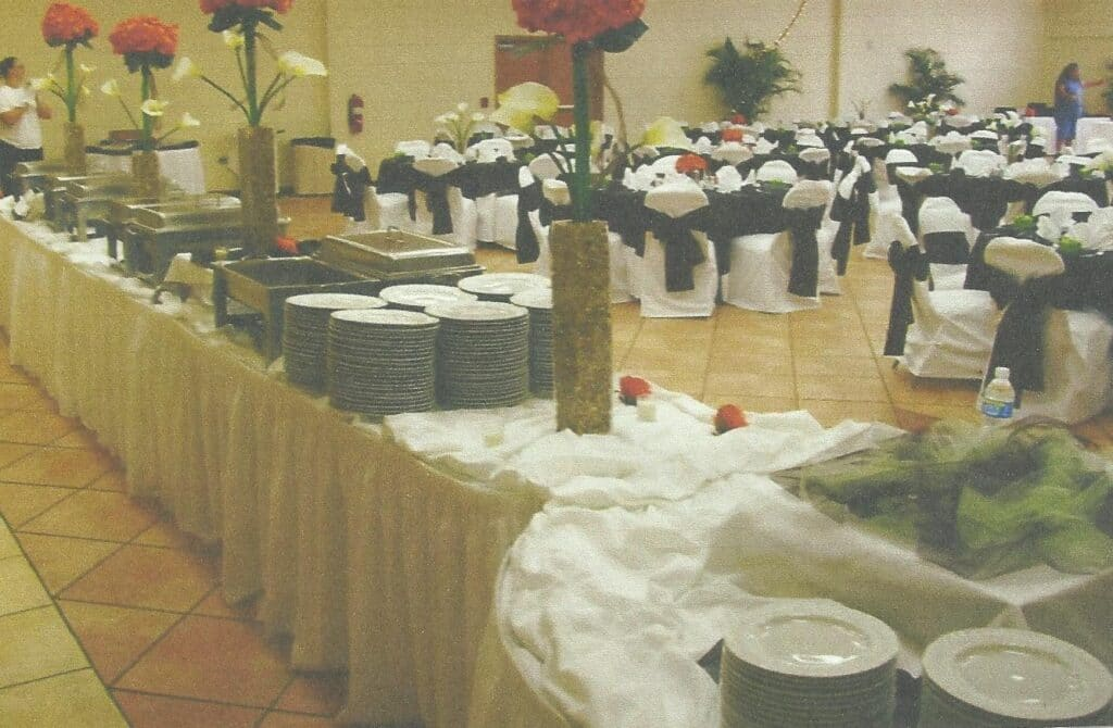 indoor wedding reception with buffet set up, round tables, and white chairs with black sashes