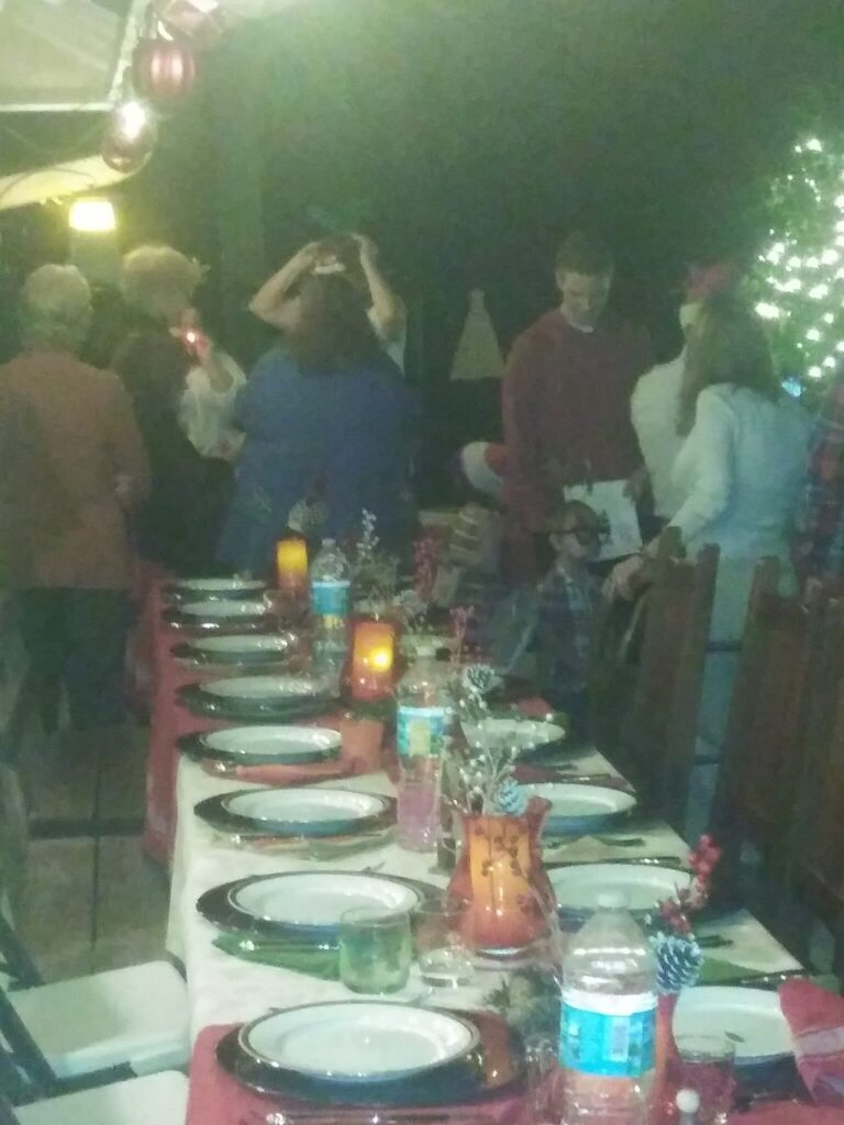 wedding guests enjoying themselves next to long table at outdoor wedding reception at night