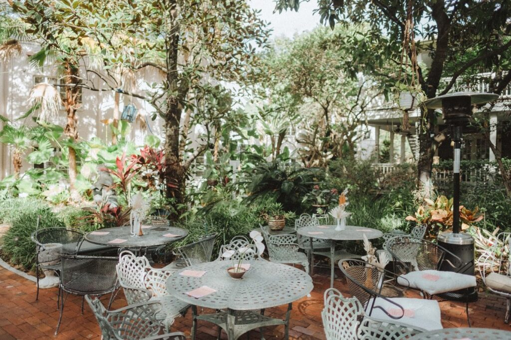 outdoor garden with brick patio and white tables and chairs
