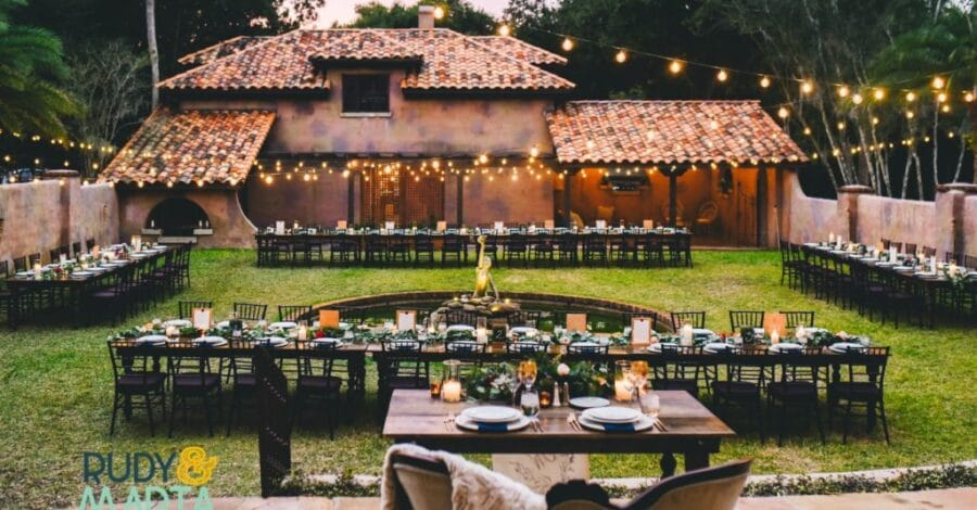 outdoor courtyard with market lighting hung and pond with statue in it in the middle of the space long rectangle tables placed in square formation around pond and small table closer to front of image