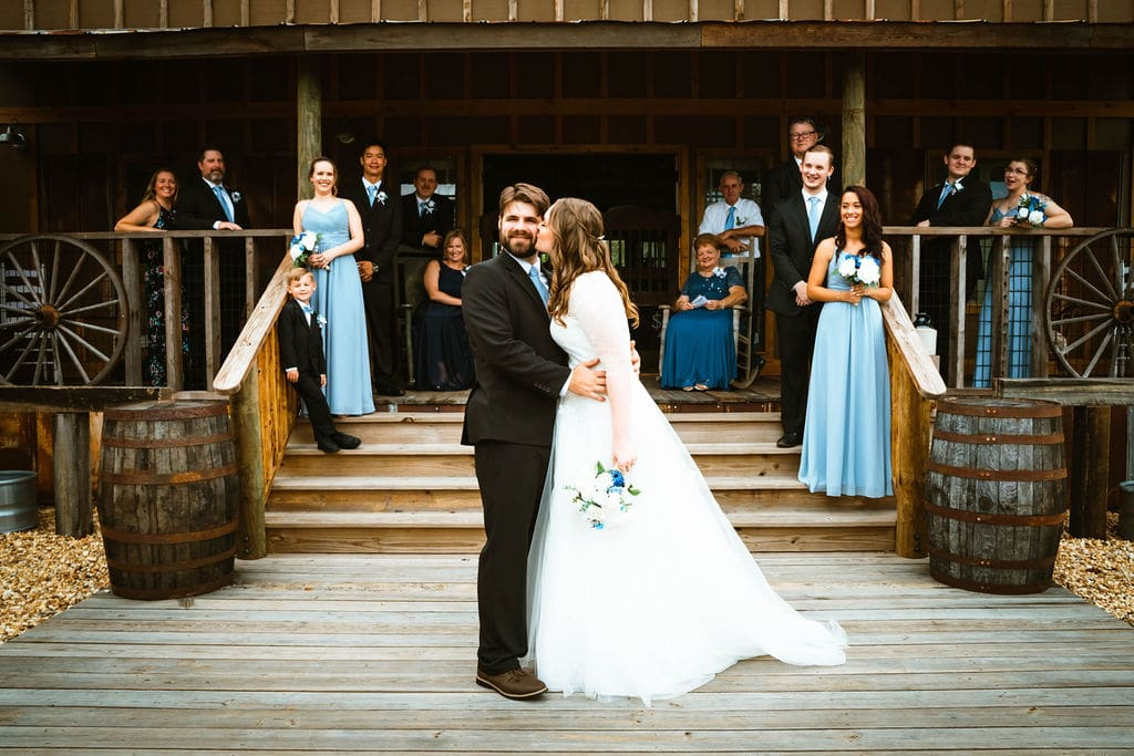 bride kissing groom on cheek while guests look on from big porch