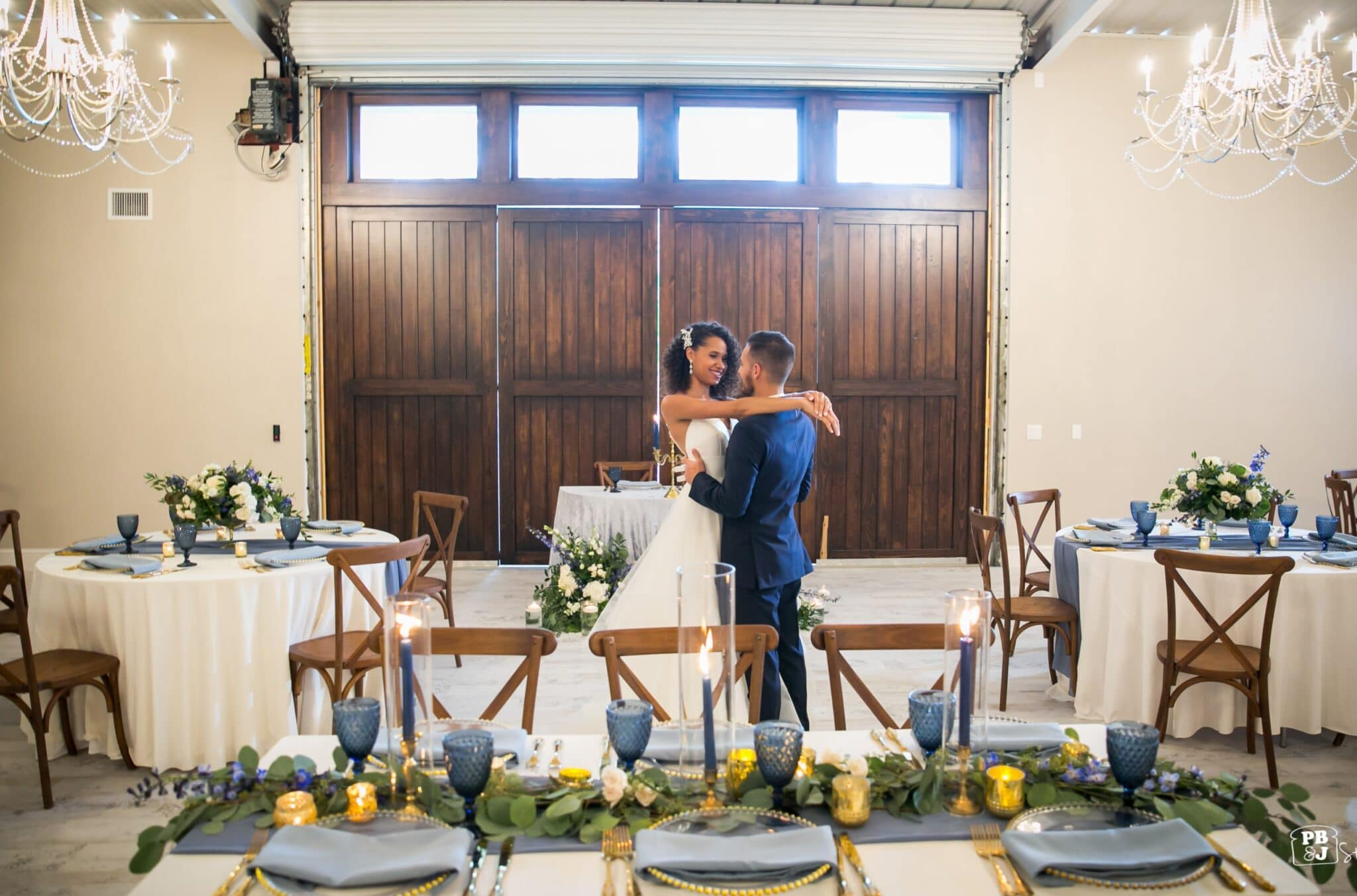 bride and groom dancing in barn below chandeliers