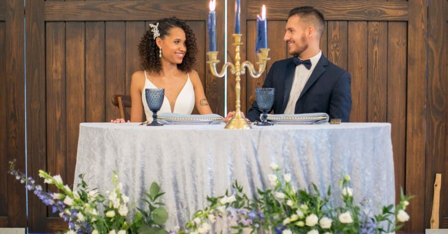 bride and groom seated at sweetheart table with blue linens and matching blue candles