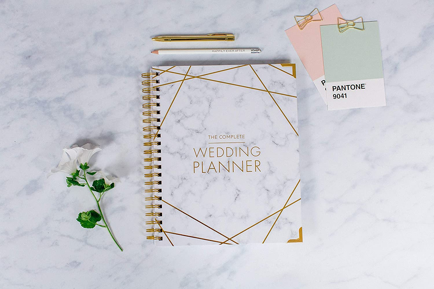 marble and gold wedding planning spiral book with single stem flower sitting to the left and pantone color swatches in the top right corner on marble surface