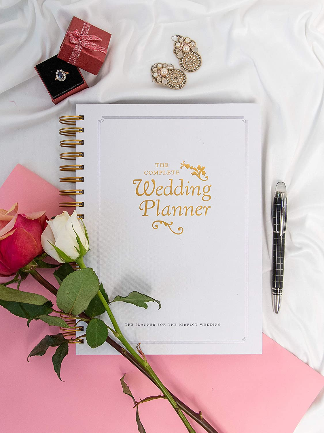 wedding planner spiral book on white cloth material with pen to the right of it and earrings at the top in the bottom corner two single stem roses white and pink