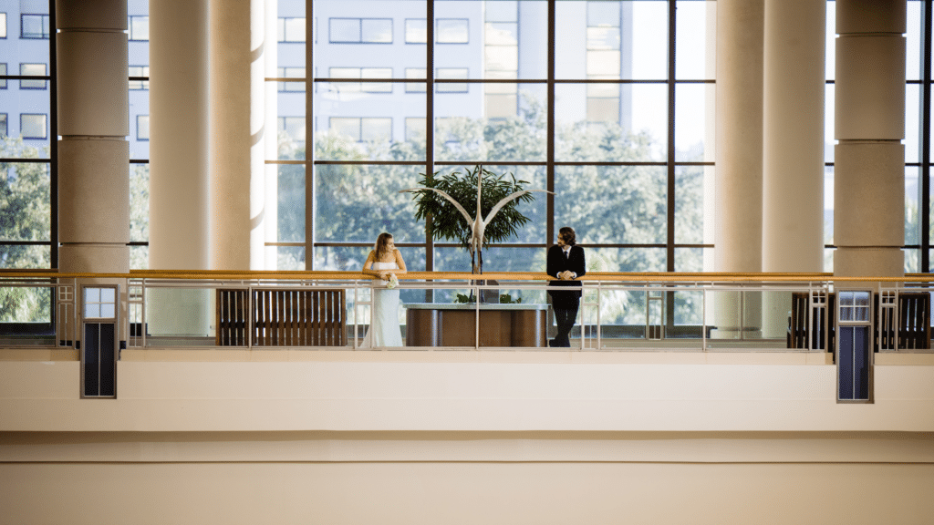 bride and groom leaning over railing looking at each other at the Orange County Convention Center