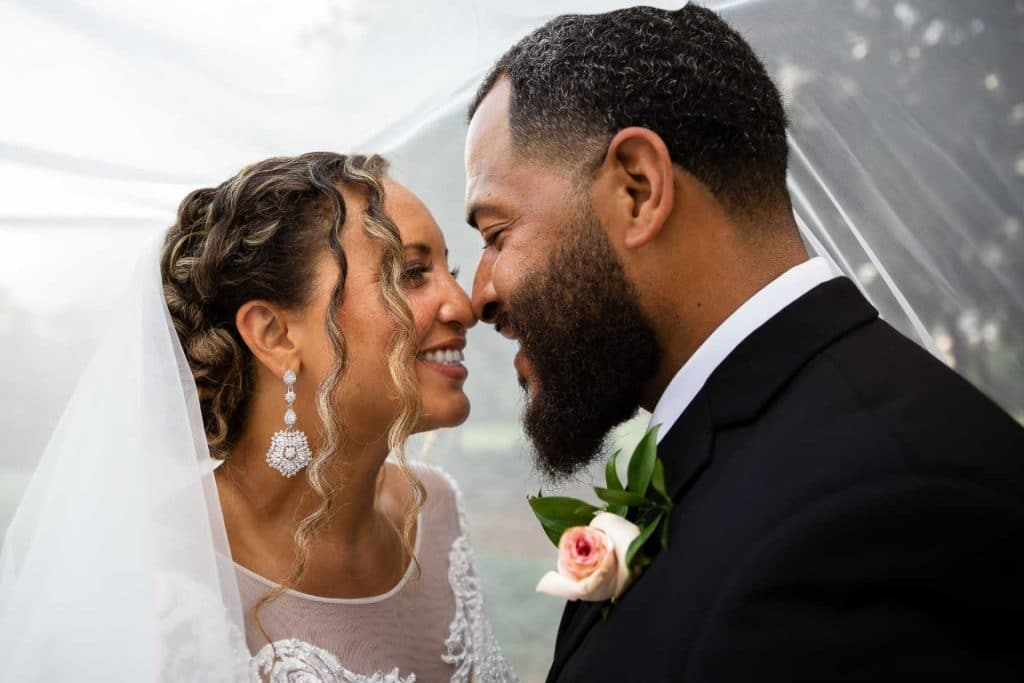 couple on wedding day stand touching noses and smiling at each other under veil for wedding portrait