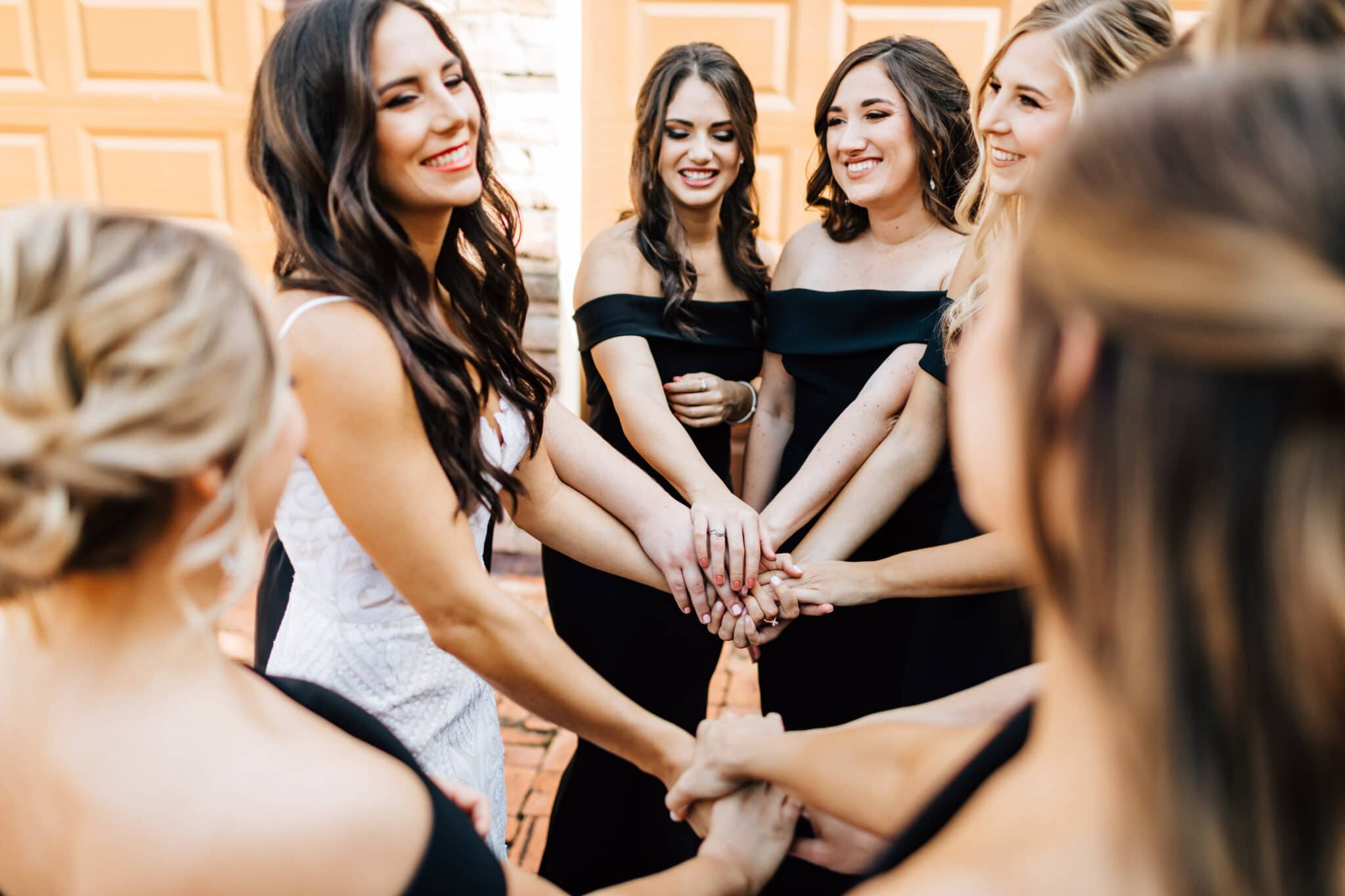 bride with bridesmaids holding hands