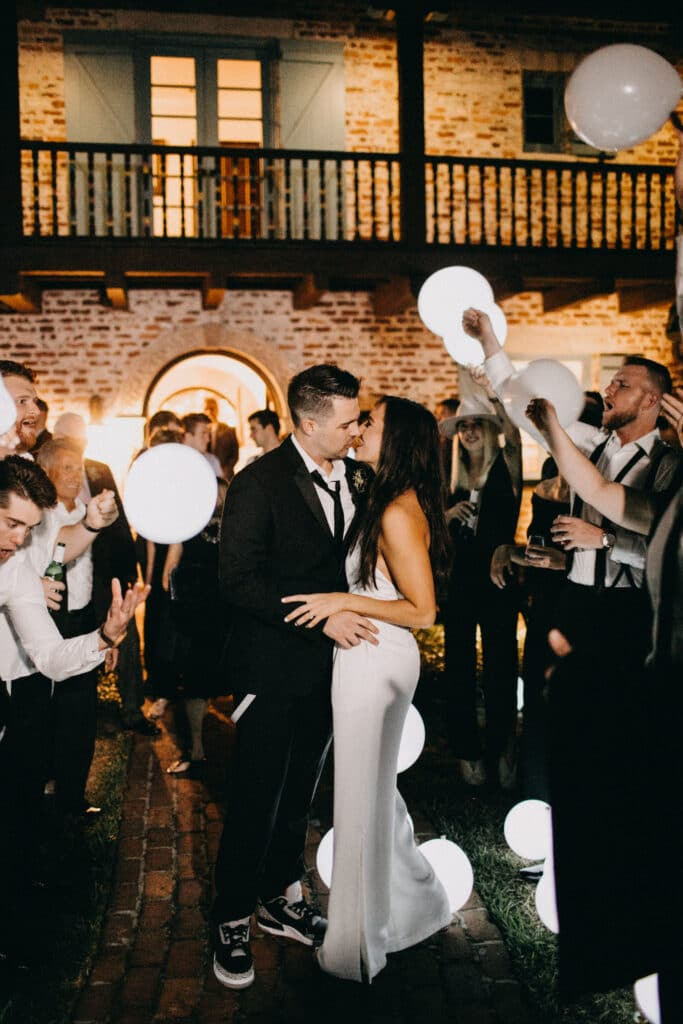 bride & groom kissing outside with guests throwing balloons