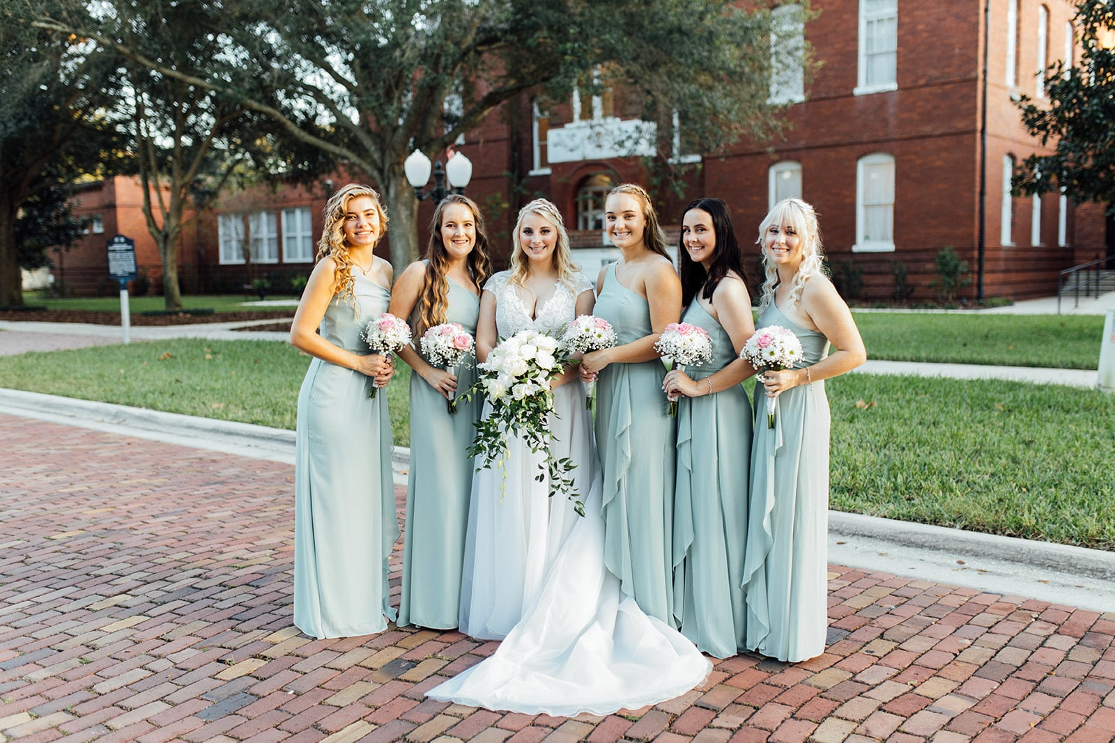 bride with five bridesmaids stands outside old school house as wedding venue holding white colored floral bouquets and smiling