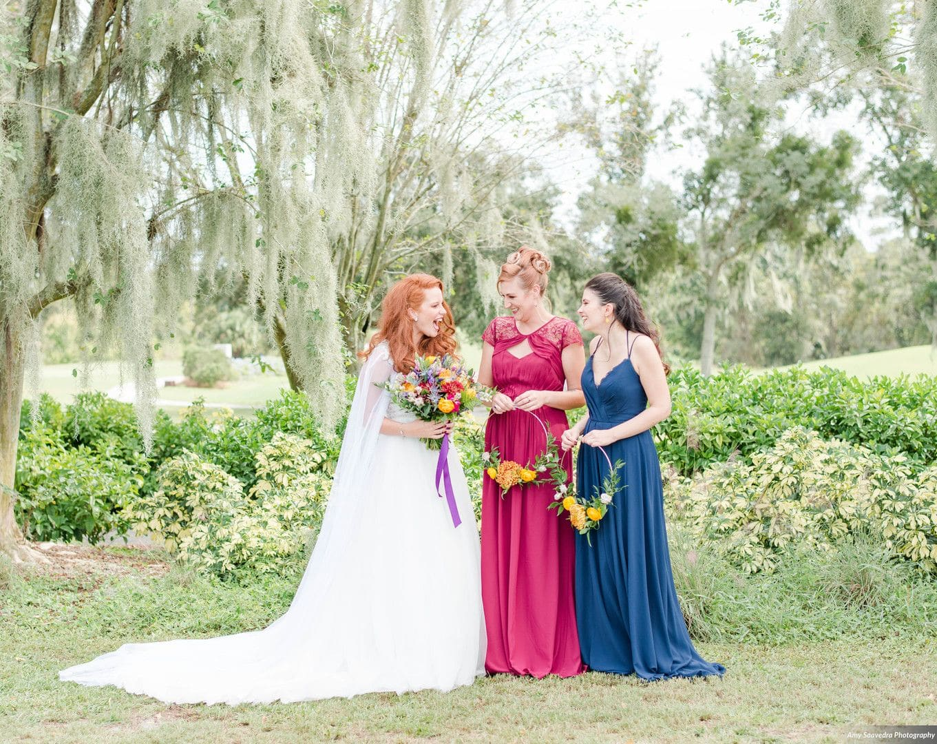 red haired bride with wedding dress on and white cape stands to the left looking to the right at two woman in teal and magenta dress holding hoop floral bouquets