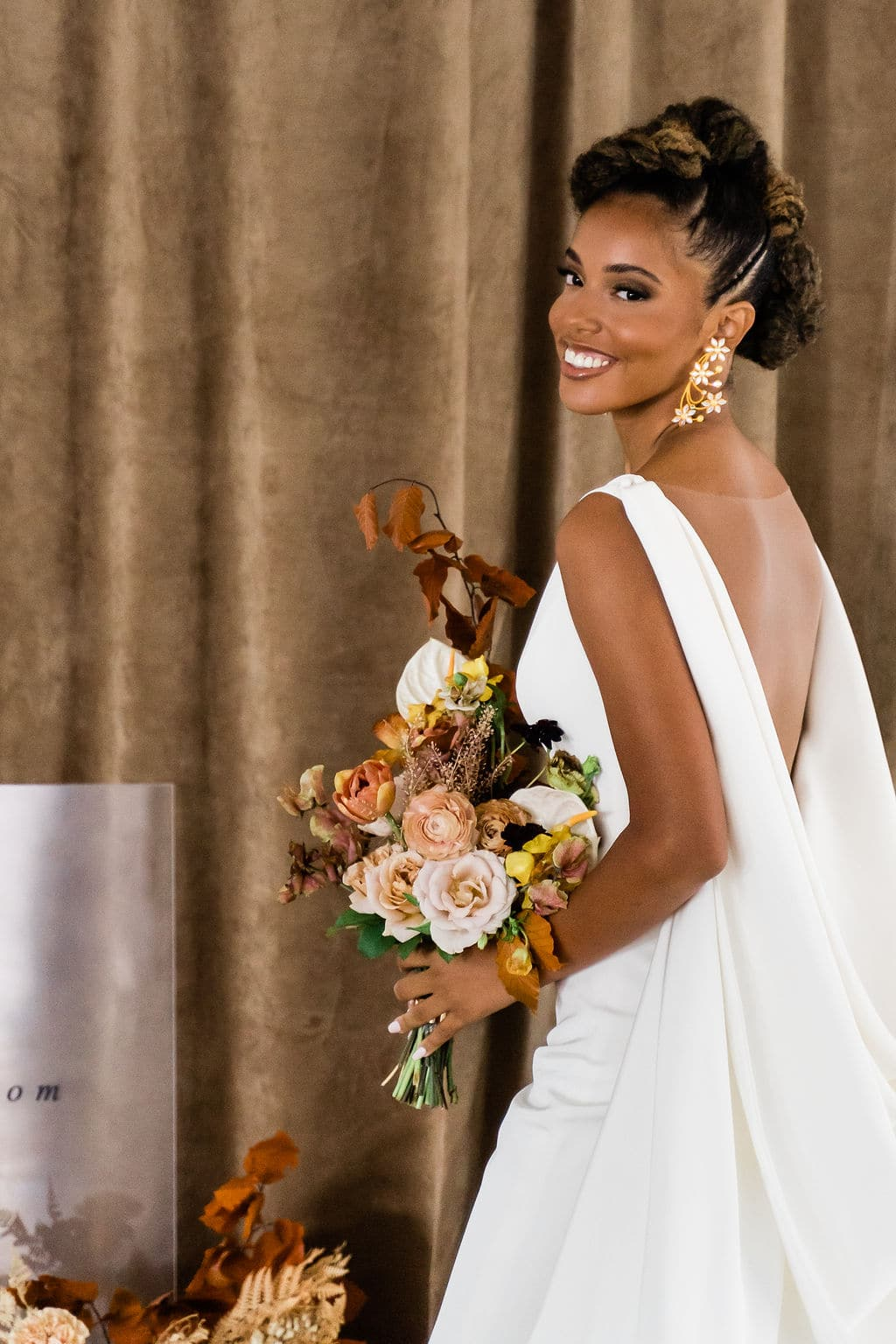 african woman wearing backless wedding dress smiling and holding a bouquet with neutral tone flowers in front of her