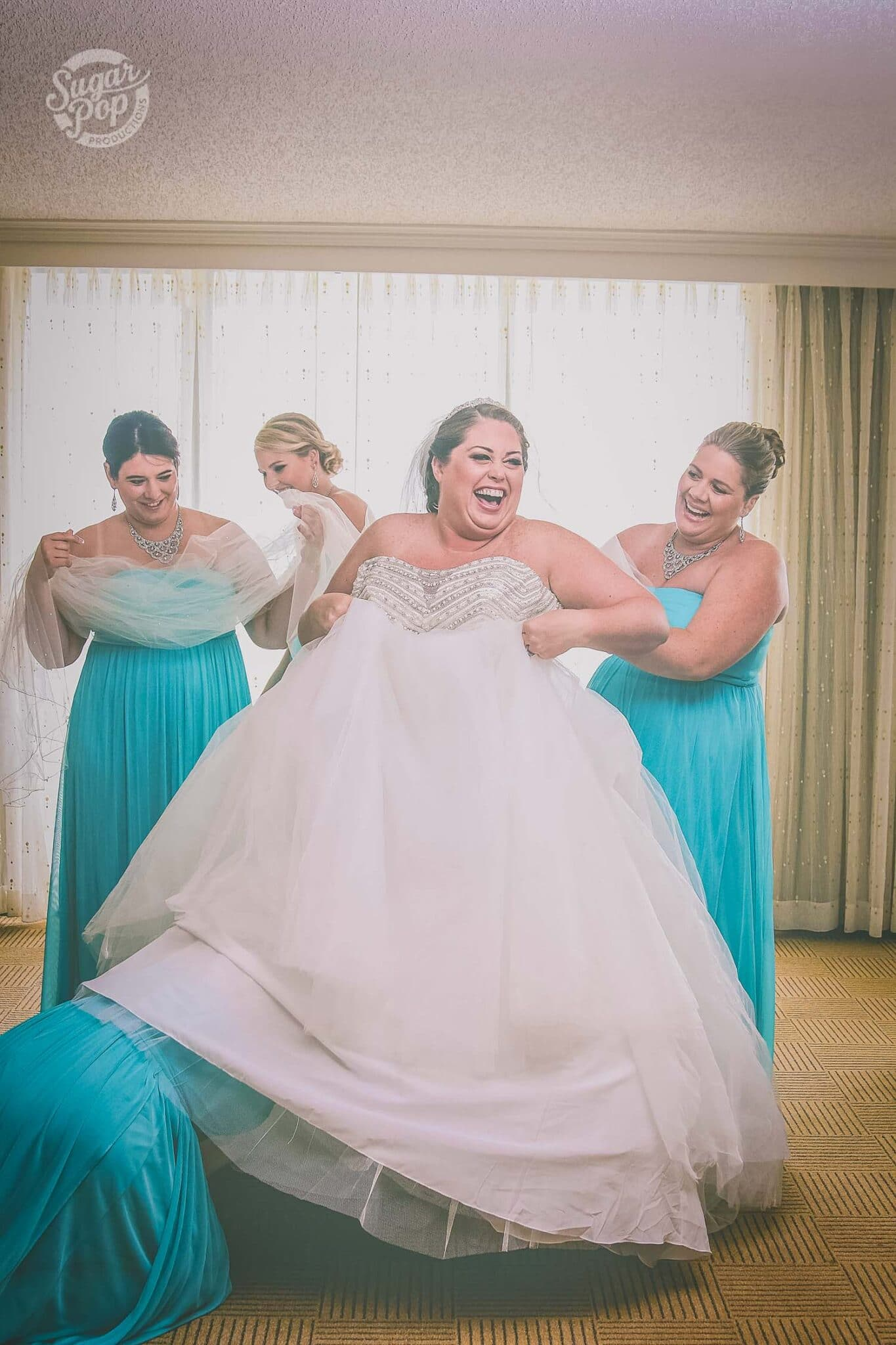 bride laughs as she holds up her big ball gown wedding dress for a bridesmaid to go under and her other three bridesmaids helping her all wearing teal