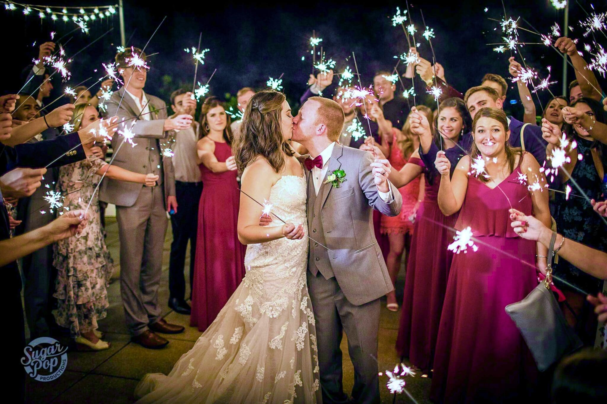 husband and wife kiss on wedding day while holding sparklers as guests around them hold sparklers too