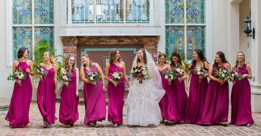 bride in white dress walking with bouquet walks next to bridesmaids in hot pink dresses with five on each side of her all carrying bouquets