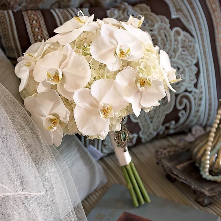close up of all white bouquet mostly with white orchids leaning against something