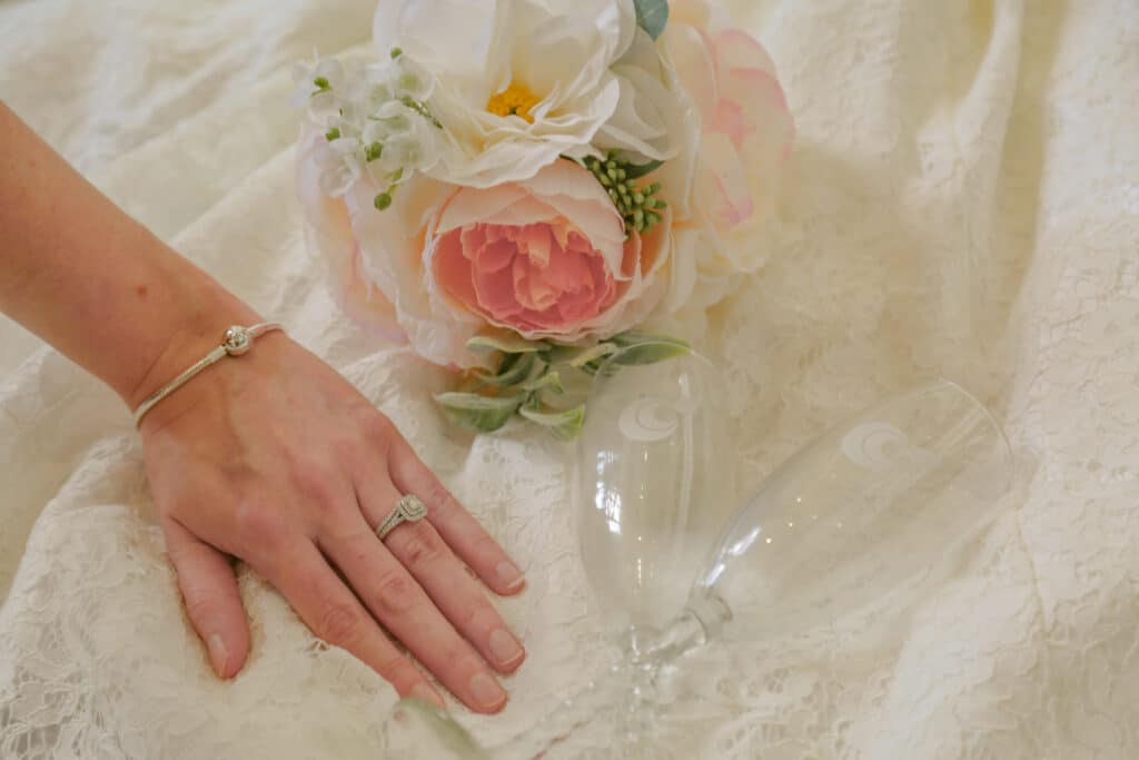 bride showing off her engagement wring and matching bracelet with her flower bouquet and matching champagne flutes laying on her dress