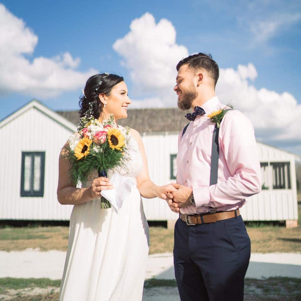 bride and groom holding hands smiling outside of old farm house