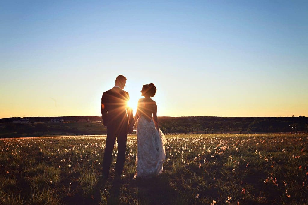 bride and groom stand on their wedding day outside in open outdoors while sunsets in front of them and they look at each other