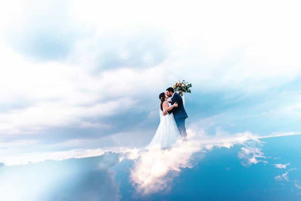 bride and groom standing on a cloud with blue sky and bride holds bouquet