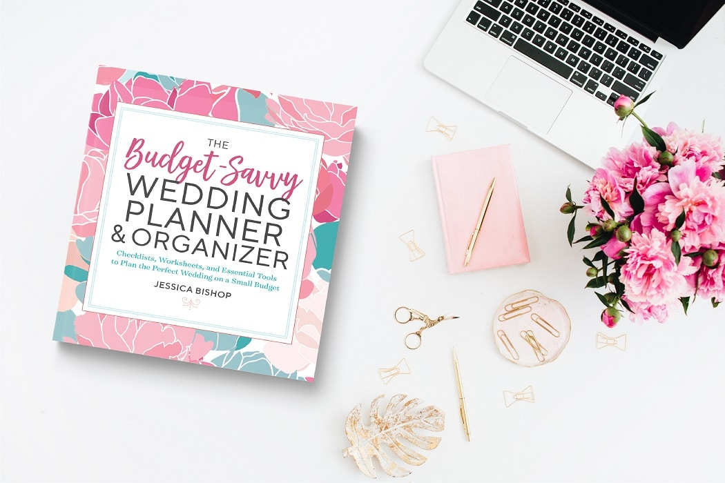 book to handle wedding planning stress next to laptop in the top right corner of the image and pink flower arrangement