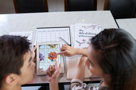 couple look at each other while sitting at desk with wedding planning papers and information out in front of them discussing a drawing on one paper