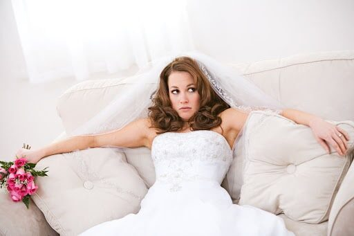 bride with hair down ad veil on sits frustrated on beige couch holding bright pink flowers with arm outstretched