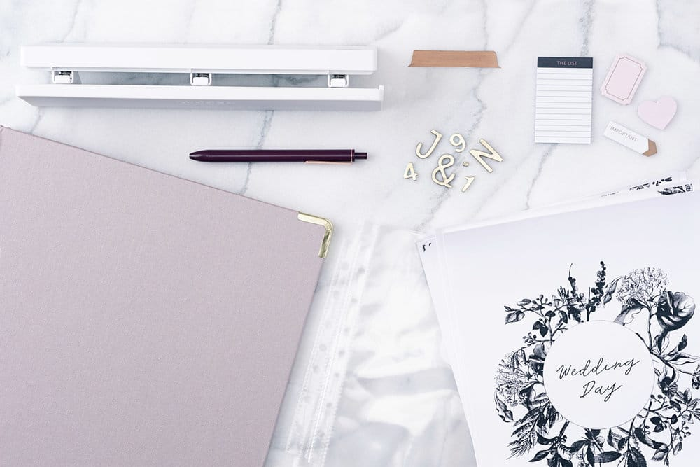desk items on space with pale pink binder to the left of the image and a hole punch at the top and a wedding day print out on the right bottom corner