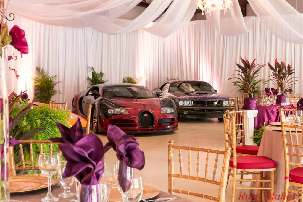 red and black sports cars inside wedding reception venue with white curtains and tropical plants