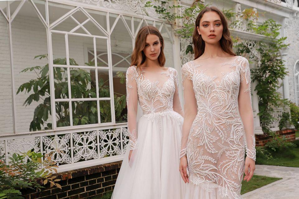 two women standing in wedding dresses