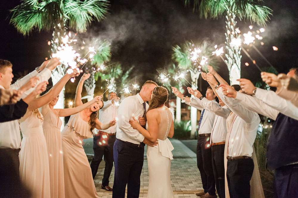 bride and groom kissing while guests hold sparklers above them