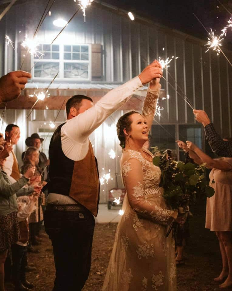 bride and groom holding hands and dancing in front of barn while guests hold sparklers around them after wedding