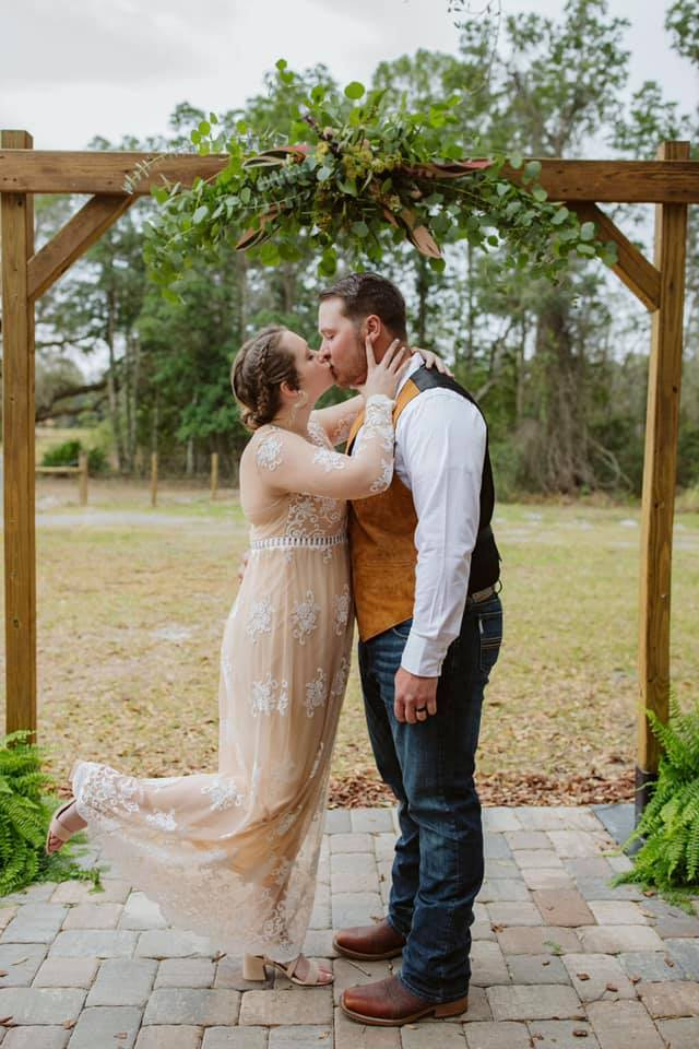groom and bride kissing with brides foot popped up behind her at outdoor farm wedding under wooden arch