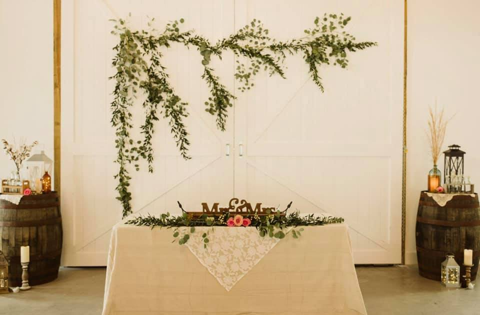 white table with green and pink floral garland with barrels decorated on either side and large green floral decor hanging on wall