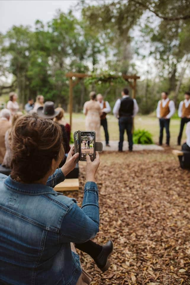 outdoor wedding ceremony under wood arch and large trees with guests looking on and taking photos on their phones