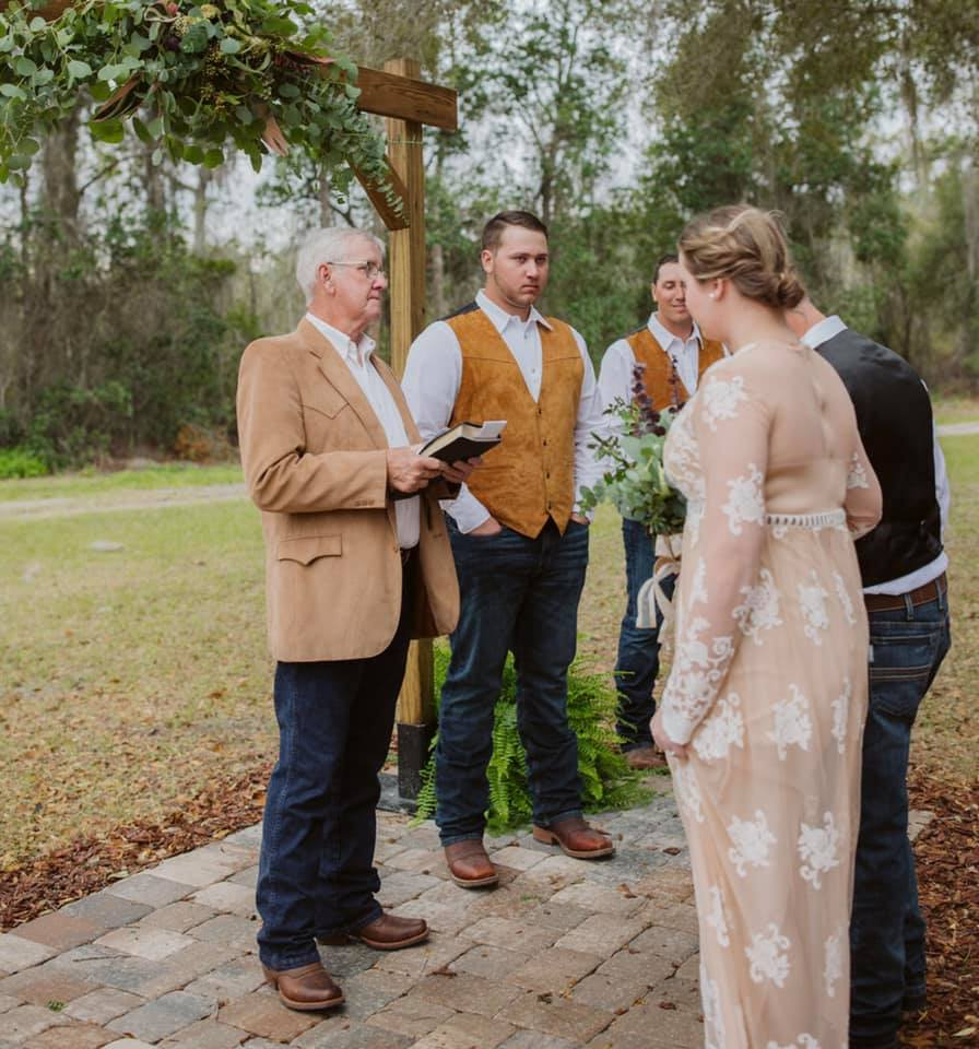 bride in white lace dress and groom with black vest standing at outdoor wedding ceremony with officiant under wooden archway
