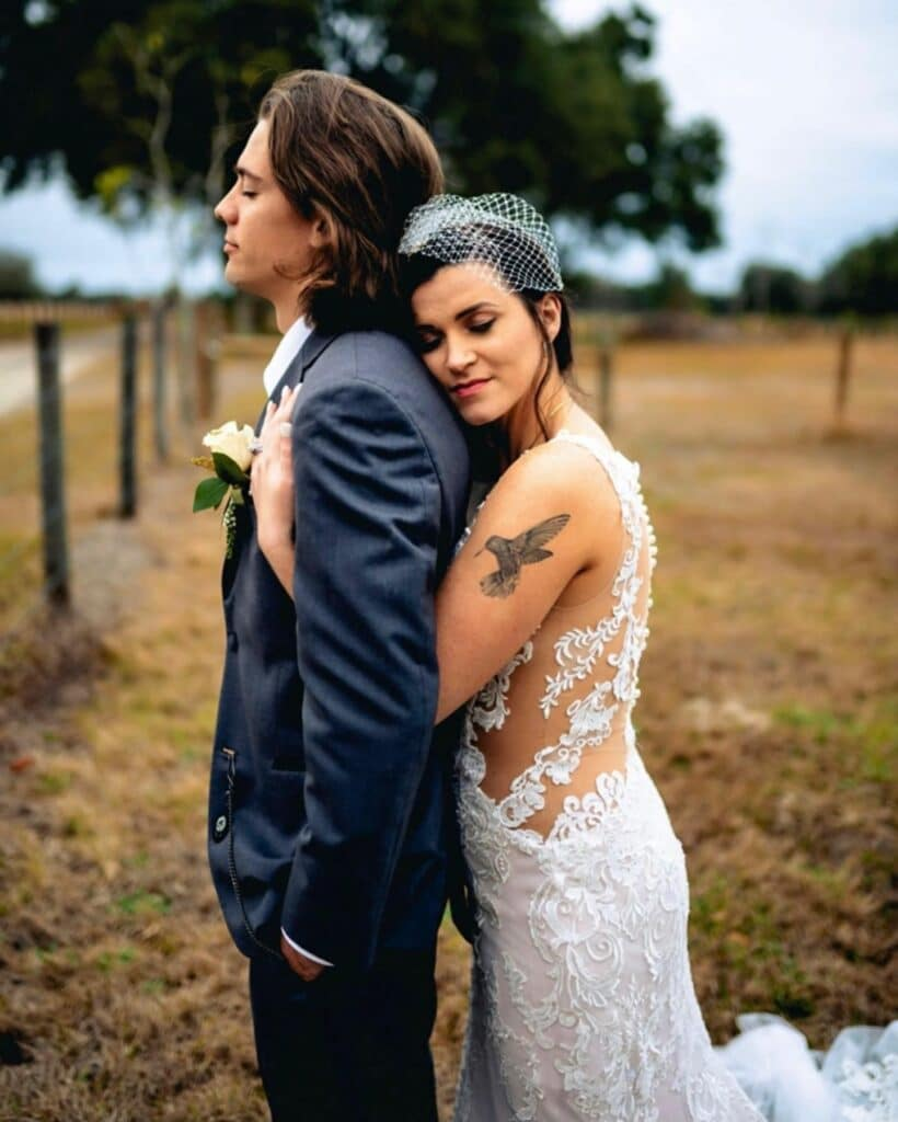 bride with bird tattoo standing behind groom with arms around him outside at farm wedding