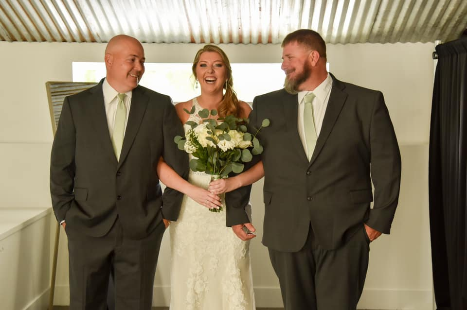 bride holding white bouquet and smiling while being escorted by two men in gray suits