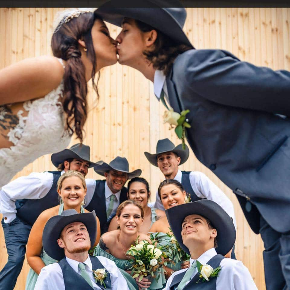 bride and groom kissing with groomsmen in cowboy hats and bridesmaids looking on