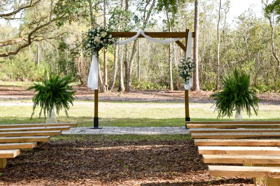 wooden archway with white draping and green floral garland in front of wood benches for outdoor farm wedding