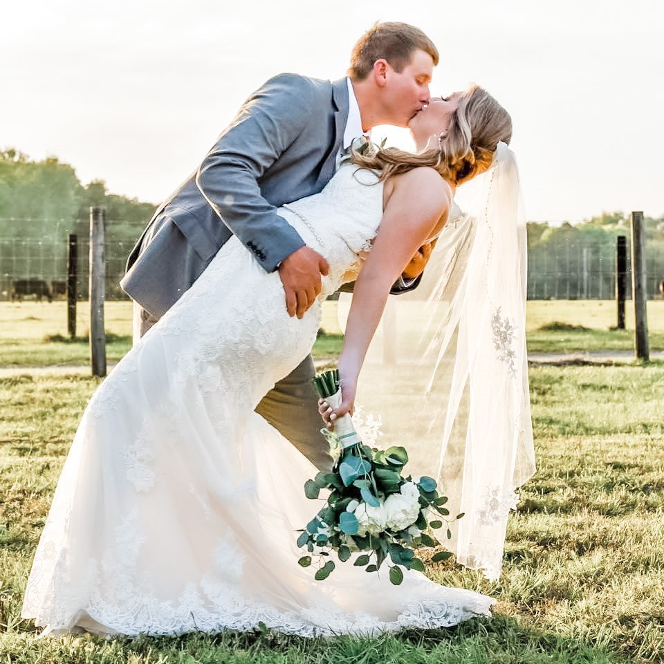 groom in gray suit leaning to kiss bride with lace dress outdoors on farm