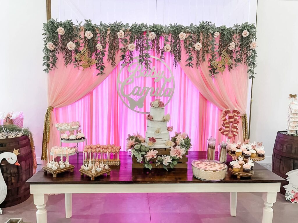 brown and white table showcasing variety of cakes and desserts in front of pink curtain at wedding
