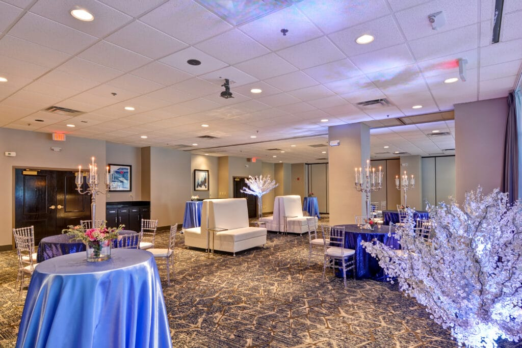 lounge with round tables with blue linen, white chairs and sofas, large mirrors, and white floral arrangements