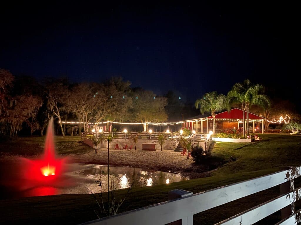 outdoor wedding venue with fountain lit up in pond, market lights, and red barn with palm trees